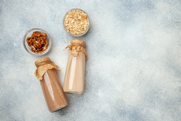 Flatlay with glass bottle of nut milk and nuts top view