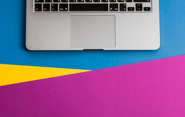 Flatlay with keyboard of laptop on three tone solid color yellow, violet and light blue ba