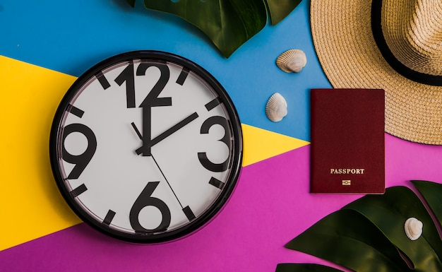 Flatlay with monstera leaves, clock, passport, straw hat on three tone background.