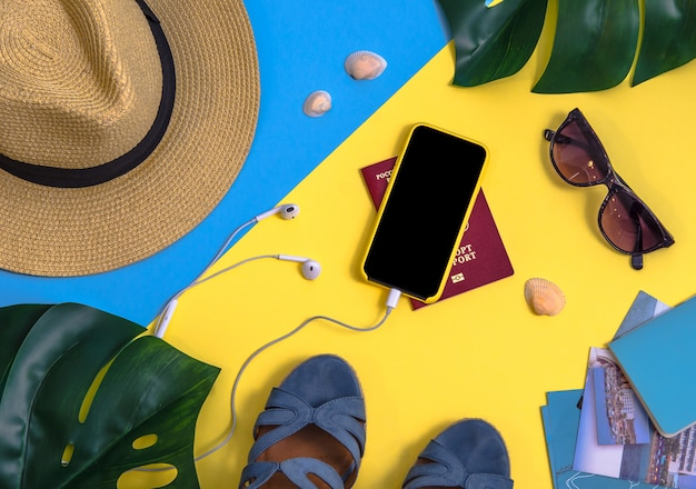 Flatlay with monstera leaves, smartphone, headphones, straw hat and other accessories