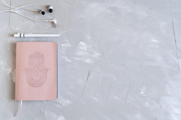 메모장, 펜 및 헤드폰 flatlay입니다. 사업 계획. 회색 바탕에 핑크색 노트북