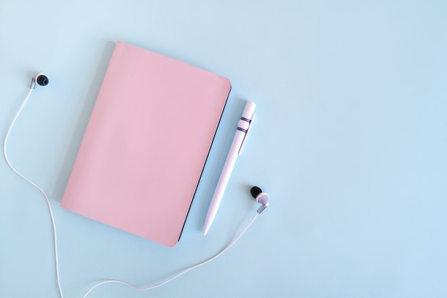 Flatlay with notepad, pen and headphones. planning your business. pink notebook on a blue background