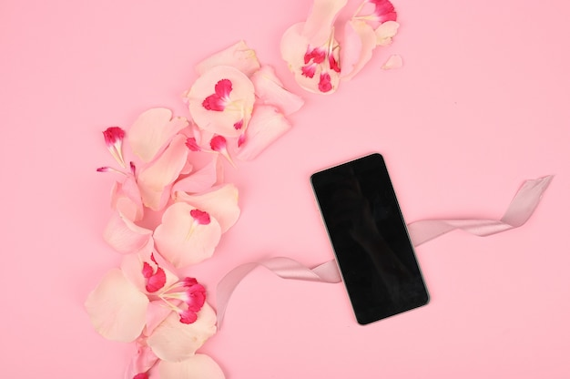 Flatlay with smartphone mock up and floral pattern at pink space. spring shopping concept. top view.