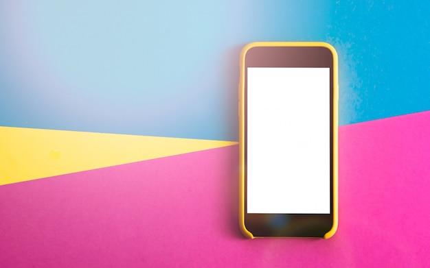 スマートフォンとフラットレイは、3つのトーンのベタ色の黄色、紫色、薄い青色の背景