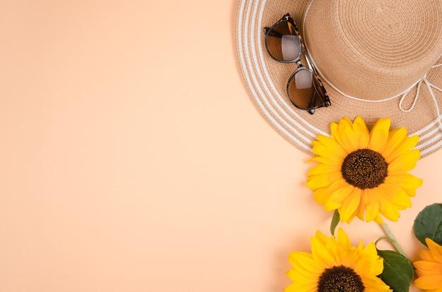 サングラス、麦わら帽子、黄色の背景に明るい黄色のヒマワリとフラットレイ。