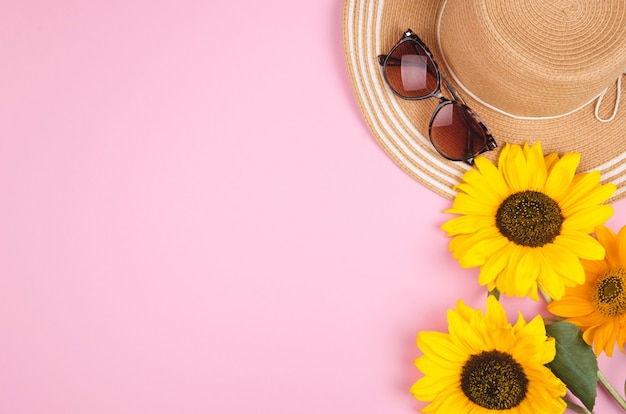 Flatlay with sunglasses, straw hat and bright yellow sunflower on pink background.