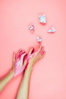 Flatlay с женскими руками, покрытыми белой и красной краской и тесной бумагой на розовом, креативная концепция