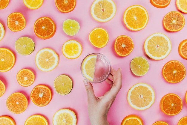Flatlay of woman's hand holding lemon water on pink background with various sliced citrus fruits