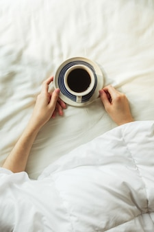 Flatlay of woman's hands covered by blanket holding cup of black coffee on a bed