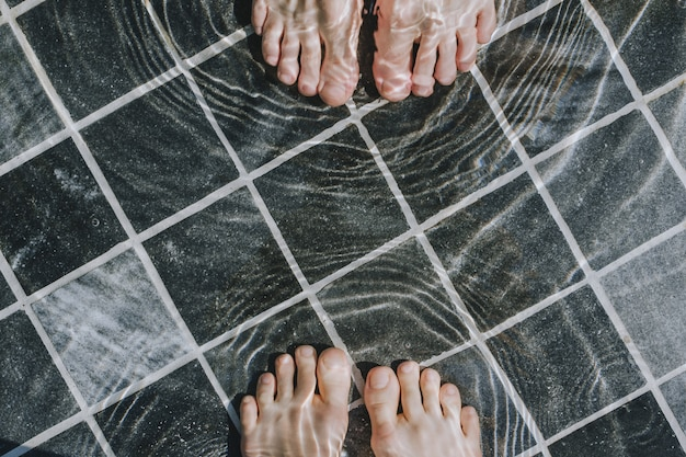 Flatlay of woman's and man's feet in a pool with dark stone tiles, holiday concept