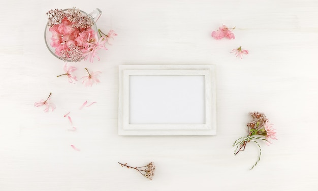 Flatlay wooden frame  with pink flowers