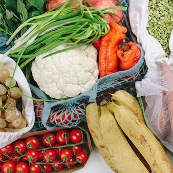 Flatlay of zero waste sustainable food shopping: grapes, tomatoes, peas, greens, hazelnuts
