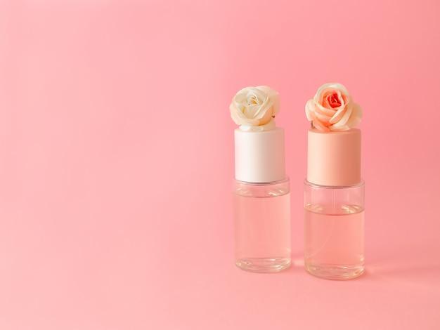 Flatlay флаконов духов с розами на розовом фоне.