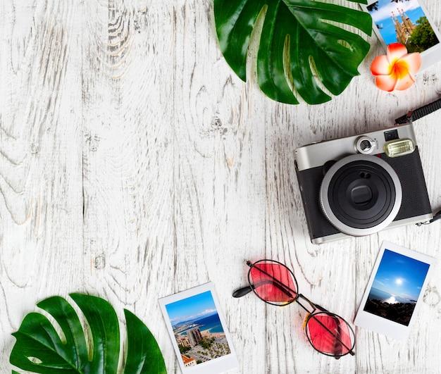 Flatlay с камерой, фото, солнцезащитные очки, листья на белом столе.