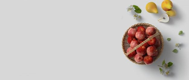 Вид сверху flatlay со здоровой пищей, фруктами, красными яблоками, грушами и цветами на белом