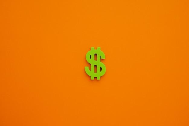 Символ американского доллара на оранжевом фоне. flatlay зеленые деньги