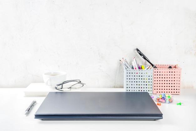 Офис творческий стол с поставками и чашка кофе. белый офисный стол с ноутбуком, клавиатурой, пустой блокнот, очки, расходные материалы и чашка кофе. flatlay макет копировать пространство вид сверху
