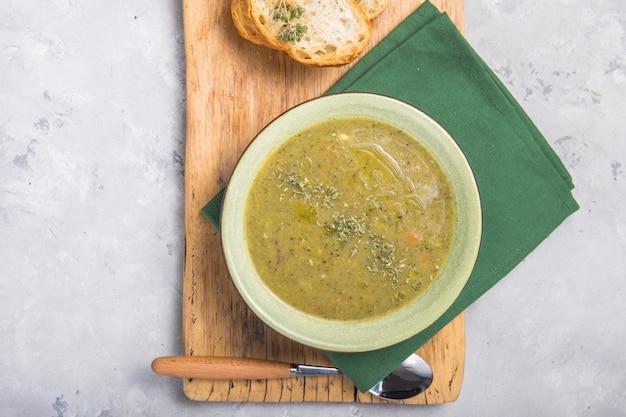 ブロッコリースープのピューレとバゲットのトーストスライスと葉状の油を添えて、上から、flatlay、コピースペースで木の板のビュー