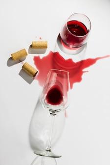 こぼれたワイン、グラス、白い背景の上の木製ワインコード。 flatlay、白い背景