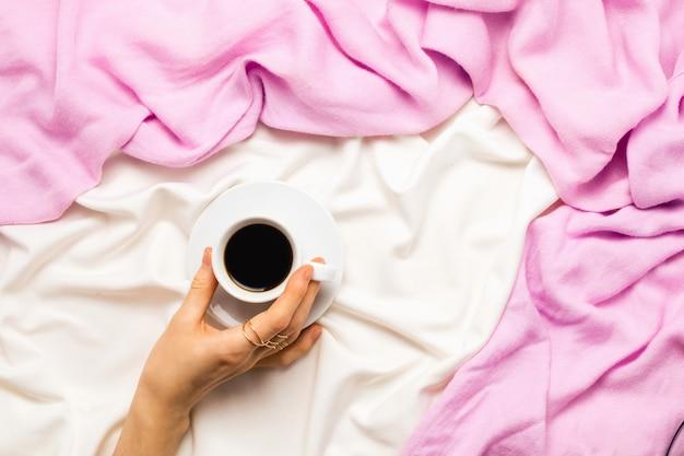 ベッドで朝のコーヒーのカップを持っている女性の手で美しいflatlay。上面図