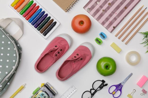 白い壁、教育の概念と学校に戻るに分離されたバックパック、学生の本、靴、カラフルなクレヨン、眼鏡、教育と教育の白いテーブルの創造的なflatlay