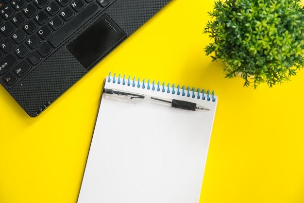 ノートパソコン、緑の植物、ペン、明るい黄色の背景上のノートブックのflatlayモックアップ。テキストのためのスペースの計画の概念