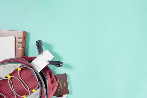青いパステルの上の世界旅行トップビューflatlayの梱包書類とガジェット