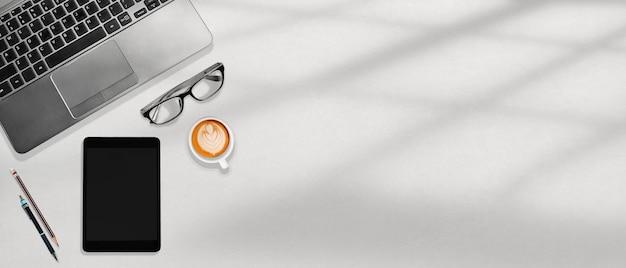 最小限のオフィスワークスペースflatlay、ラップトップ、タブレット、コーヒー、ウィンドウライト