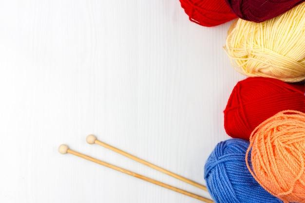 色とりどりのパステル調のかせの毛糸と編み針の白い背景の上のflatlay