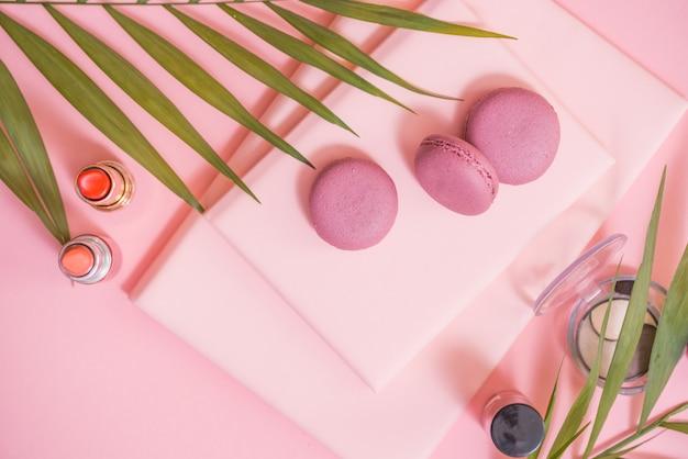 ピンクのテーブルにノート、ケーキマカロン、花のflatlay。マカロンと美しい朝食