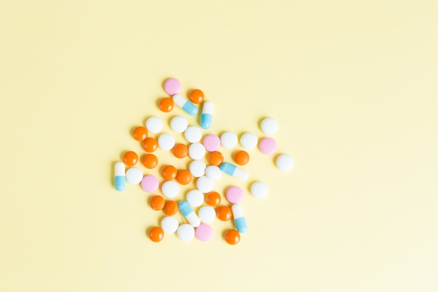 Различные различные таблетки, таблетки на желтом фоне. многие таблетки и таблетки с пространством для текста. здравоохранение. вид сверху. копировать пространство фармацевтическая картина. flatlay. хороший фон