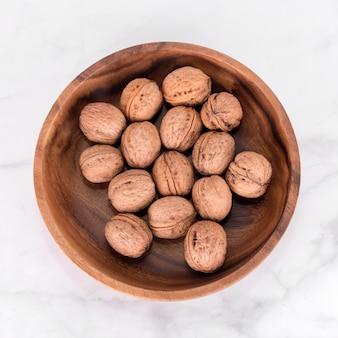 Грецкий орех в деревянной миске на светлом фоне мрамора. flatlay, вид сверху. деревянная тарелка с грецкими орехами
