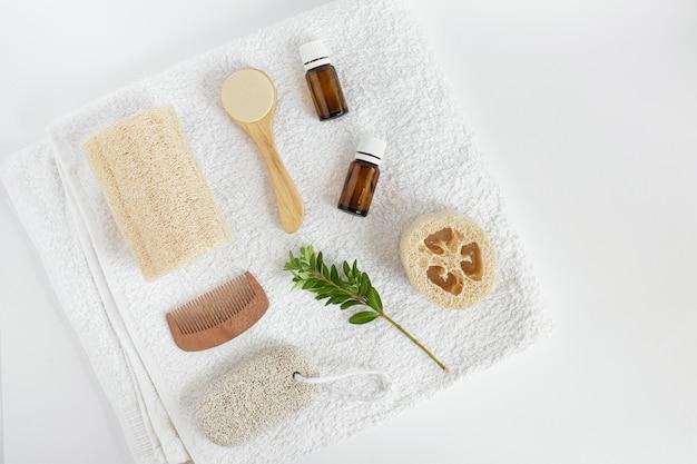 Лепешка с натуральными предметами для ухода за собой. люфа, стеклянные бутылки, пемза, люфа, средство для умывания, расческа на белом полотенце. спа продукты