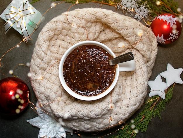 Flatleyはスカーフと休日の装飾の中でコーヒーが入ったマグカップです