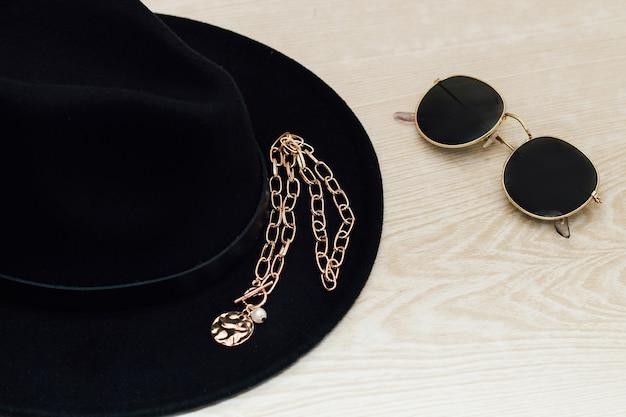 Флэтли в черной шляпе, очках, украшениях.