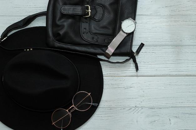 Флэтли в черной шляпе, очках, часах, сумке.