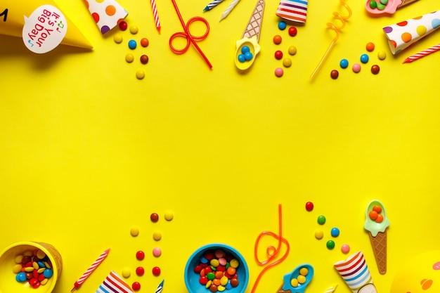 テキスト用のコピースペースがある黄色のテーブルのフラットアウト誕生日パーティーカード。