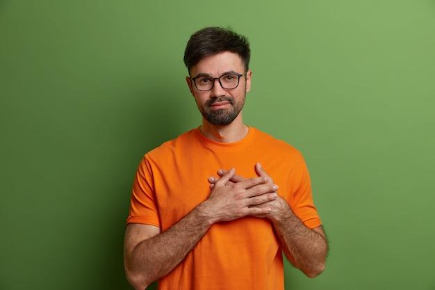 Lusingato e soddisfatto ragazzo con la barba lunga preme le mani sul cuore, esprime sentimenti commoventi e gratitudine apprezza la lode indossa occhiali trasparenti e maglietta arancione brillante isolato sul muro verde
