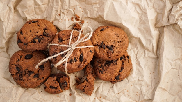 Flatview of handcrafted chocolate cookies with chocolate chips on baking paper. natural handmade organic snakes for healthy breakfast