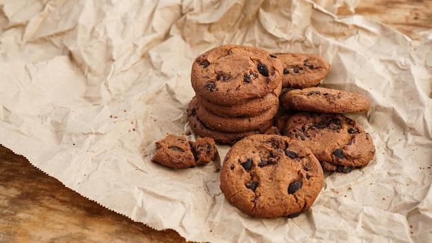 Плоский вид шоколадного печенья ручной работы с шоколадной стружкой на бумаге для выпечки. натуральные органические змеи ручной работы для здорового завтрака