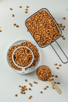 Flavored coffee seeds in coffee pot, cup and black colander on a white surface. flat lay.