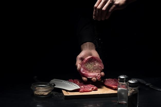 フレーバーのもの。レストランで料理やシェフとして働いている間、肉にスパイスを効かせる男の手のクローズアップ。