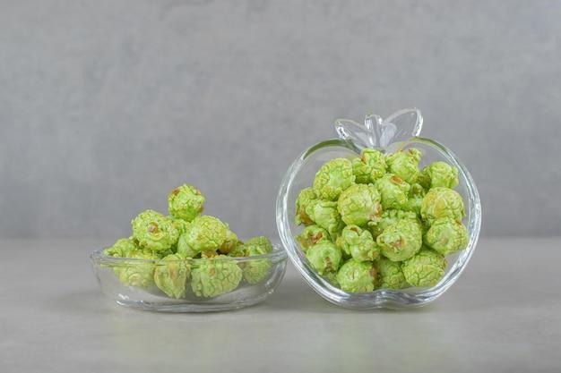 大理石のテーブルの上のリンゴの形をしたキャンディーホルダーに詰められた風味のポップコーン。