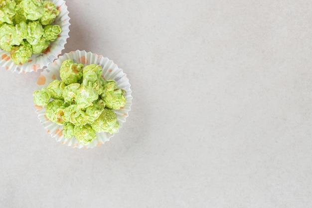 Ароматизированный попкорн, разложенный по порциям для пирожков на мраморном столе.