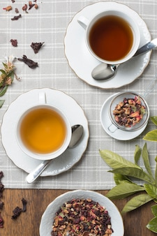 Flavored tea cups with dried tea herbs on wooden table cloth