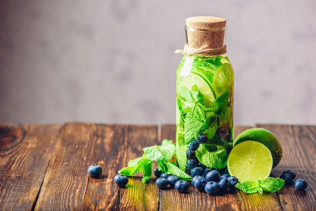 Flavored water in bottle with lime, mint and blueberry and ingredients