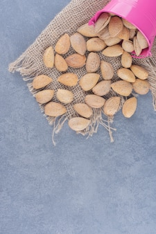 Flavorful almonds spill out of a bowl, on the marble background.