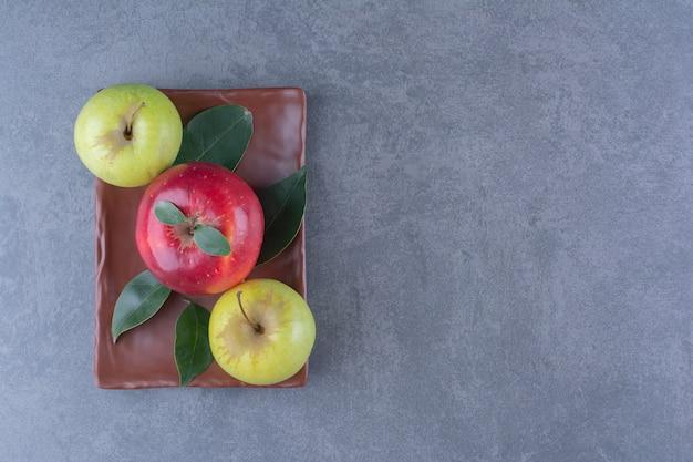 어두운 표면에 나무 접시에 잎과 맛있는 사과