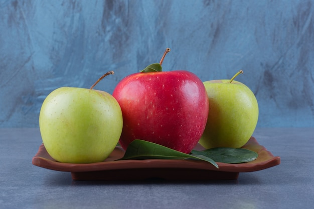Flavorful apples with leaves on wooden plate on the dark surface