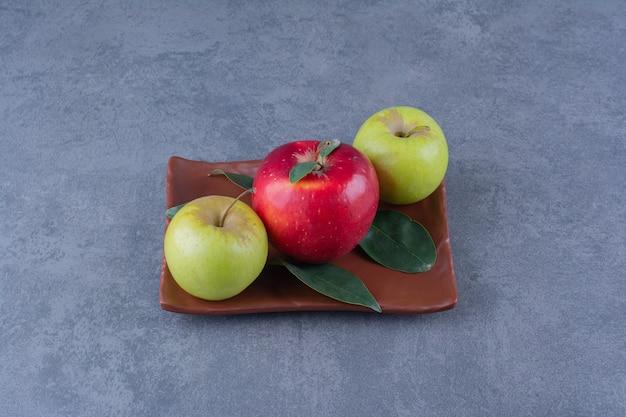 Mele saporite con foglie su piatto di legno su tavola di marmo.
